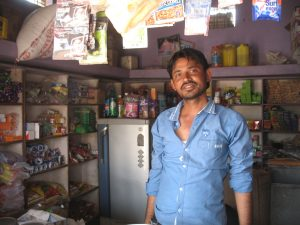 This shopkeeper is one of the many happy people with little to their name.